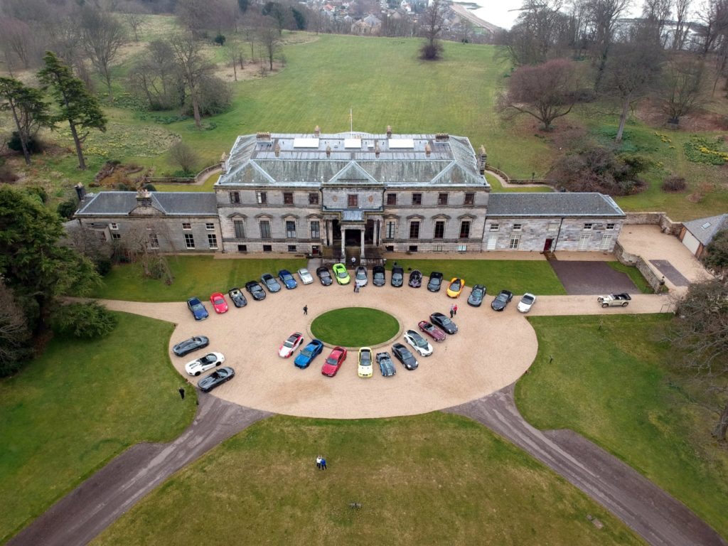 Looking down from overhead at a Country estate with supercars lined up n the driveway