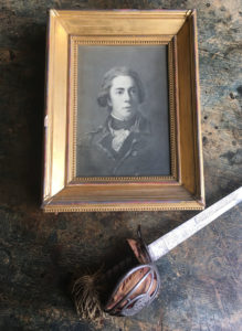 Portrait picture lying next to a sword