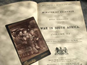 Photo of a man sitting with two boys lying on top of a book titled 'War in South Africa'