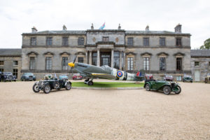 two cars in front of a country estate