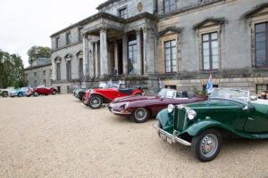 classic cars in front of country estate