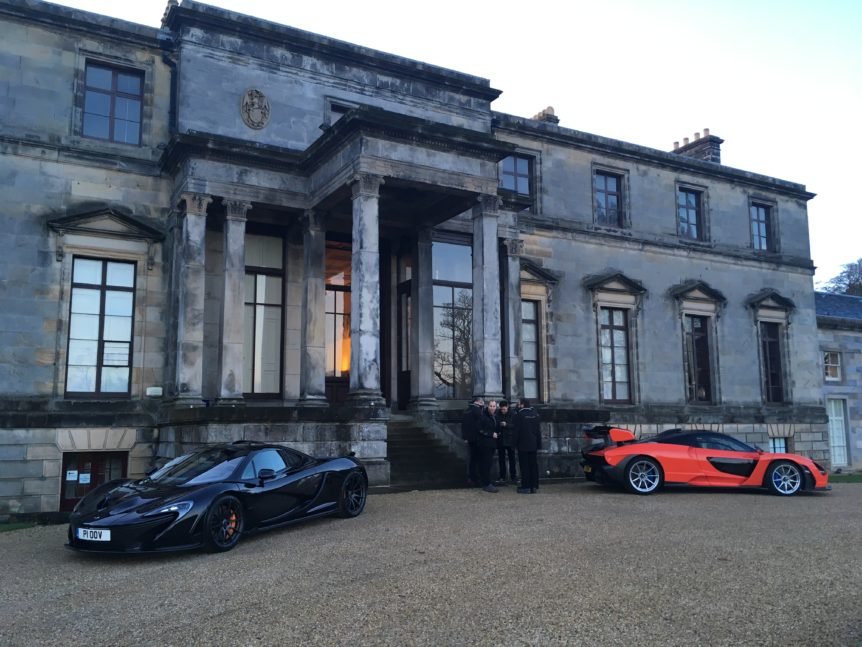Two supercars outside a country estate